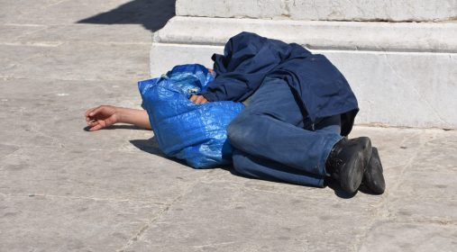 A homeless man sleeps in the street in broad daylight